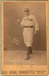 A baseball player is standing, facing the camera, holding a baseball.