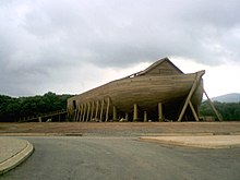 The fully constructed ark is at the center of the image with a downcast sky. A large ramp on the left side of the image is leading up into the ark. In the foreground of the image is a paved street.