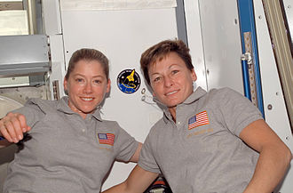 STS-120 - Two commanders: Melroy and Whitson place the STS-120 mission insignia on the wall of the newly installed Harmony module.