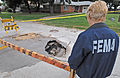 FEMA - 32288 - FEMA worker looks at a Sink Hole in a road from flood.jpg