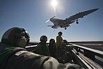 Flight deck crewmen watch as an F-A-18C Hornet aircraft prepares to land aboard the aircraft carrier USS Carl Vinson (CVN 70) as the ship conducts flight operations in the Pacific Ocean on Feb 130213-N-ZI635-048.jpg