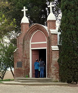 Photograph of the Grand Island Shrine, with two women standing in the gothic-arch doorway
