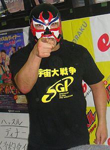 A color photograph of a Japanese man in a black mask with a white front and red and blue markings pointing at the camera
