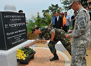 Hill 303 massacre - U.S. and ROK soldiers lay roses at the foot of the memorial established on Hill 303.