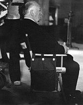 Image of Hitchcock seated during the filming of Family Plot