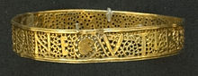 A gold bracelet with a pattern and writing. The upper and lower edges are solid, but between them is a lacey pattern made of leafy plant tendrils. Amidst this mostly perforated pattern, letters are formed from solid gold segments.