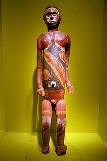 An image of a brown wooden standing male figure partially painted with large black, yellow and white pigment, figure is in an exhibition case on a green background
