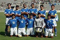 Foto von elf Männern, sechs stehend und fünf kniend, in einem Stadion