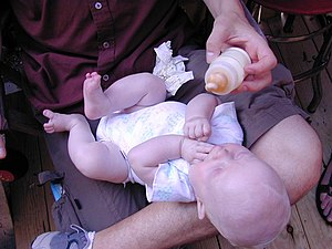 A baby having milk from a bottle.