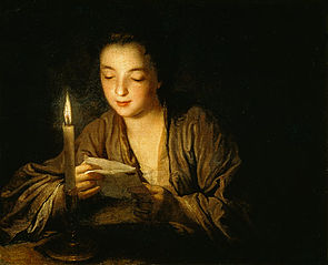 Girl reading a letter by candlelight
