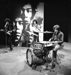 A black and white photo of three men performing onstage. Behind them is a wall with a bigger picture of them on it.