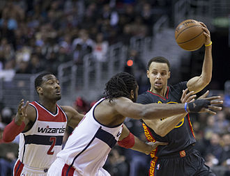 Stephen Curry - Curry about to pass while being guarded by John Wall and Nenê of the Washington Wizards. Curry averaged 7.7 assists per game during the 2014–15 NBA regular season, good enough for sixth best in the league.
