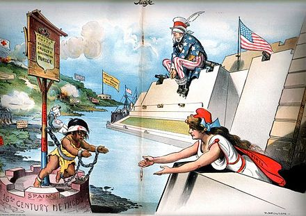 Editorial cartoon intervention in Cuba. Columbia (the American people) reaches out to help oppressed Cuba in 1897 while Uncle Sam (the U.S. government) is blind to the crisis and will not use its powerful guns to help. Judge magazine, February 6, 1897. Judge-2-6-1897.jpg
