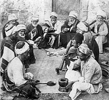 An old photo of a dozen old and middle-aged men sitting on the ground around a mat. A man in front sits next to a mortar and holds a bat, ready for grinding. A man opposite to him holds a long spoon.