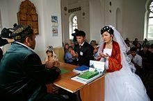 Photo en couleur montrant un imam face à un couple (l'homme est en costume-cravate, la femme en robe blanche avec un voile orange); derrière, une trentaine de personnes assises.