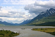 A large body of water, much longer than wide, lies at the base of mountains with vestiges of snow in their higher declivities. Vegetation is sparse. The mountains rise to meet a sky filled mostly with puffy white or gray clouds.