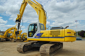 Kobelco Construction Machinery America - Kobelco SK330LC excavator with a hydraulic hammer attachment.