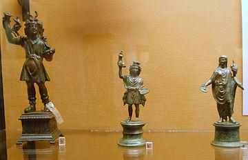 photographie de trois représentations de Lares. Toutes tiennent un plat et une corne dans les mains