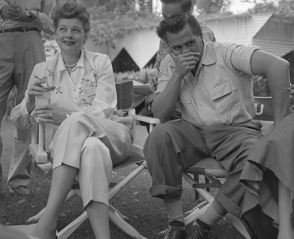 Lucille Ball and Desi Arnaz seated in directors chairs at press conference in Los Angeles, Calif., 1953