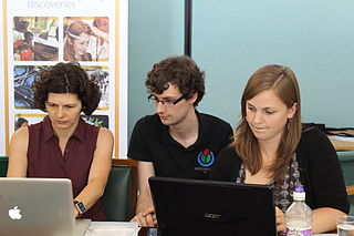 The photo shows two people editing Wikipedia with a trainer on hand to help
