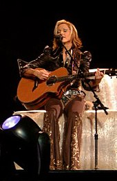 A blond woman sitting on a block of hay. She is playing a guitar and singing in front of a standing microphone, she has short hair and wears grey colored cowboy clothes.