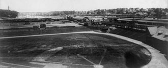Polo Grounds - Manhattan Field c. 1901 with Polo Grounds outfield in background. High Bridge crossing the Harlem River at about 173rd Street is in the background.  The bridge's center spans over the river itself were replaced by a large single span in the 1920s.  The tower on the left is Highbridge Water Tower.