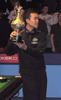 Photograph of Marco Fu standing while holding the Grand Prix trophy