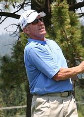 A white male with a receding hairline looks on after swinging at a golf ball with a club. He is wearing a sky blue polo shirt, golf pants, and a white cap.