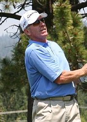 A man in a blue polo shirt and a white cap is standing on a golf course. He is wearing sunglasses as he looks after a ball he has just hit.