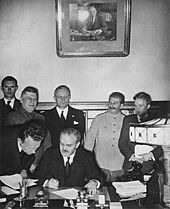 Soviet Foreign Minister Vyacheslav Molotov signs the Molotov–Ribbentrop Pact. Behind him stand German Foreign Minister Joachim von Ribbentrop and Soviet Premier Joseph Stalin.
