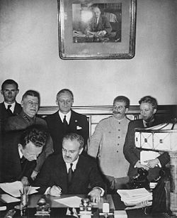 Soviet Foreign Minister Vyacheslav Molotov signs the Molotov-Ribbentrop Pact.  Behind him stand (left) German Foreign Minister Joachim von Ribbentrop and (right) Soviet Premier Joseph Stalin.