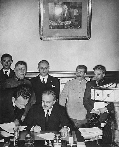 Soviet Foreign Minister Vyacheslav Molotov signs the Molotov-Ribbentrop Pact. Behind him stand (left) German Foreign Minister Joachim von Ribbentrop and (right) Soviet leader Joseph Stalin. MolotovRibbentropStalin.jpg