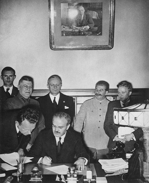 Soviet Prime Minister Vyacheslav Molotov signs the Molotov-Ribbentrop Pact. Behind him stand (left) Foreign Minister Joachim von Ribbentrop of Germany and (right) Joseph Stalin. The non-aggression pact had a secret protocol attached in which arrangements were made for a partition of Poland's territory. MolotovRibbentropStalin.jpg