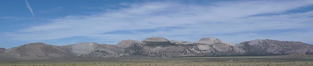 An overlapping series of gray domes with sharp peaks. Scrubland in foreground.