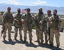 A color image of six military personnel dressed in their combat uniforms and holding weapons.