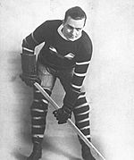 Hockey player, with a large capital M on the front of his sweater, leans over his stick posing in typical fashion for a photo