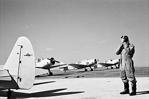 Pilot in flying suit standing by four single-engined military monoplanes