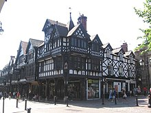 A complex range of predominately black-and-white timber-framed buildings seen from a corner.  To the left is a range of shops with an arcade at ground level and windows and decorated gables above.  The building on the corner has four gables of differing size and height and a spire; this building has a painted effigy in the corner of the middle storey.  To the right is a simpler building; it is a public house in three storeys with three dormers.