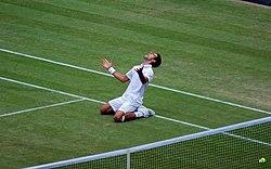 Novak Djokovic viert are 2011 Wimbledon halve finale overwinning op Jo-Wilfried Tsonga.  Overwinning betekende DAT Djokovic op 1 juli 2011 ontmoette succes pakte de ATP Wereld nummer 1 positie for the Eerste Keer in Zijn carrière HIJ bereikte also are Eerste Wimbledon finale, sterven HIJ uiteindelijk won.