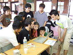 OLPC with children and developers.JPG
