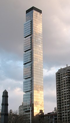 A tall, thin building with some slight squarish projections at its higher levels seen from between some trees.