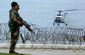 A US Military Special Operations Security Team Member observes a United Nations MI-8 Hip helicopter approaching the American embassy in Monrovia, Liberia in June 2003