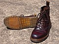 Pair of brown Dr Martens 1460 boots with the sole of one boot showing.jpg