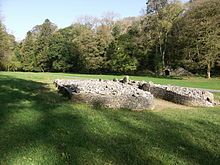 Front view of a cairn, from its right side, its boulders retained by a short wall that forms a courtyard at its entrance. The cromlech is set in flat ground of short grass (in dappled sunlight in the foreground and full sun elsewhere), dissected by a path passing behind it. Trees are mainly in leaf to its rear, among which a limestone kiln is visible at the foot of a gorge.