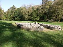 Вид спереди на пирамиду из камней с правой стороны, валуны удерживаются короткой стеной, образующей двор у входа.  Кромлех расположен на плоской земле из невысокой травы (в пятнах солнечного света на переднем плане и на полном солнце в другом месте), рассеченной тропинкой, проходящей позади него.  Деревья в основном покрыты листвой сзади, среди которых видна известняковая печь у подножия ущелья.