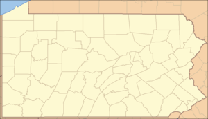 A map of the state of Pennsylvania with a red dot in the north-central part