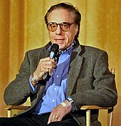 A white male in his 60s sitting in a chair while speaking into a microphone. He is wearing eyeglasses and a grey jacket over a blue buttoned down shirt. His left hand is rested on his lap.