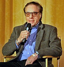 Bogdanovich seated at a director's chair with a microphone in his hand
