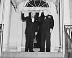 "Photograph of Winston Churchill flashing his ""V for Victory"" sign and President Truman waving outside Blair House in... - NARA - 200108 (cropped1).jpg"