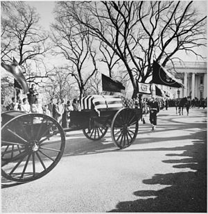 "State funeral of John F. Kennedy - A limbers and caissons bearing the casket of President John F. Kennedy seen moving down the White House drive on the way to St. Matthew's Cathedral on November 25, 1963. A color guard holding the presidential colors, the flag of the President of the United States, and the riderless horse ""Black Jack"", follow behind."